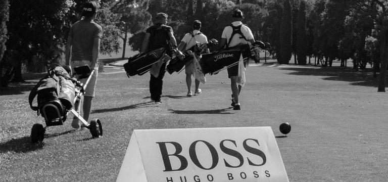 campo da golf con giocatori e sponsor hugo boss in primo piano